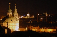 The panorama over the castle wall includes the Church of St. Nicholas, a notable example of Baroque architecture.