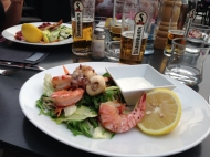 Grilled prawns and ciddlefish on lemon-dressed field greens and, yes, a local beer brand make a good dinner choice on a boat in the Vlatava River.